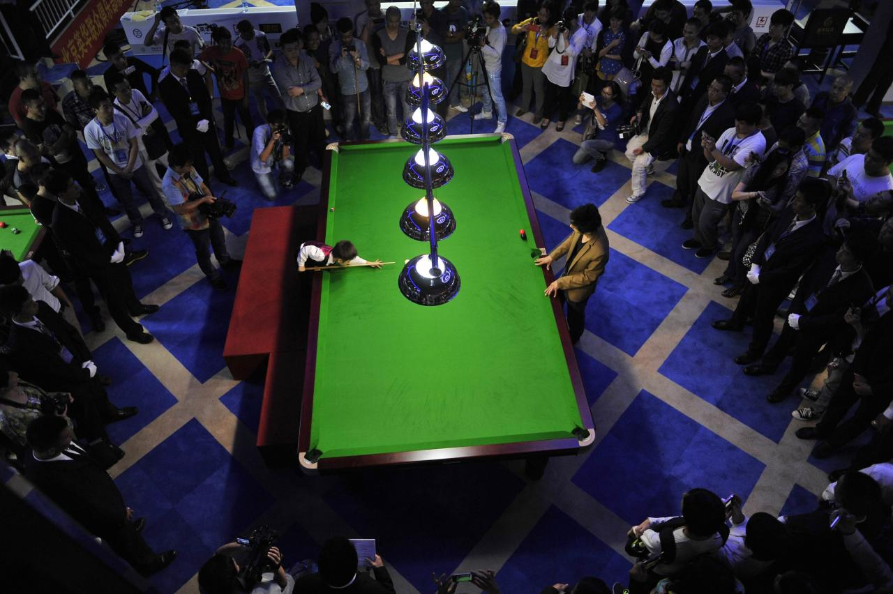 Three-year-old Wang Wuka (on L of table) plays snooker with seven-time World Championship winner Stephen Hendry (not pictured) of Britain in Beijing, September 22, 2013. Wuka's father Wang Yin, a snooker fan, has been teaching his son the sport for more than two years. The boy, who vows to be a top snooker player, undergoes five hours of training daily to shoot the balls with precision. Picture taken September 22, 2013. REUTERS/Stringer (CHINA - Tags: SPORT SOCIETY) CHINA OUT. NO COMMERCIAL OR EDITORIAL SALES IN CHINA