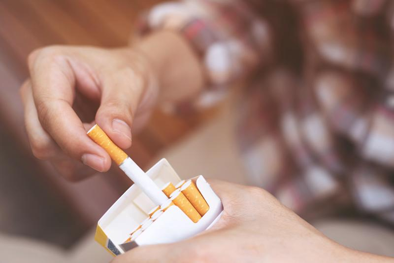 Close-Up Of Person Holding Cigarette Pack