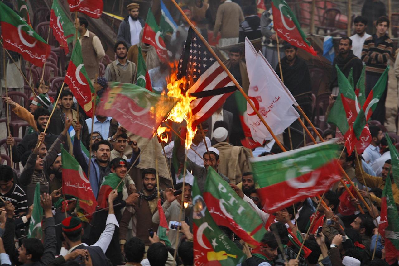Supporters of Pakistan's Tehreek-e-Insaf party, headed by cricketer-turned politician Imran Khan, wave their party's flag while burning a representation of a U.S. flag during a protest against U.S. drone strikes in Pakistan, in Peshawar, Pakistan, Saturday, Nov. 23, 2013. Thousands of people protesting U.S. drone strikes blocked a road in northwest Pakistan on Saturday used to truck NATO troop supplies and equipment in and out of Afghanistan, the latest sign of rising tension caused by the attacks. (AP Photo/Mohammad Sajjad)