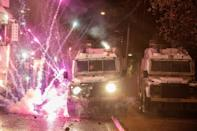 Riot police formed ranks with armoured Land Rovers, as fireworks and petrol bombs were thrown at them