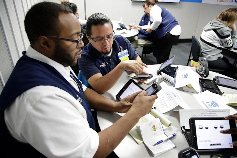 In this Thursday, Nov. 9, 2017, photo, Walmart employees Kenneth White, left, and Marvin Toc work together using an inventory app while participating in a class at the Walmart Academy at the store in North Bergen, N.J. The retail industry is being radically reshaped by technology and nobody feels that disruption more starkly than the 16 million Americans working as shelf stockers, salespeople and cashiers. (AP Photo/Julio Cortez)