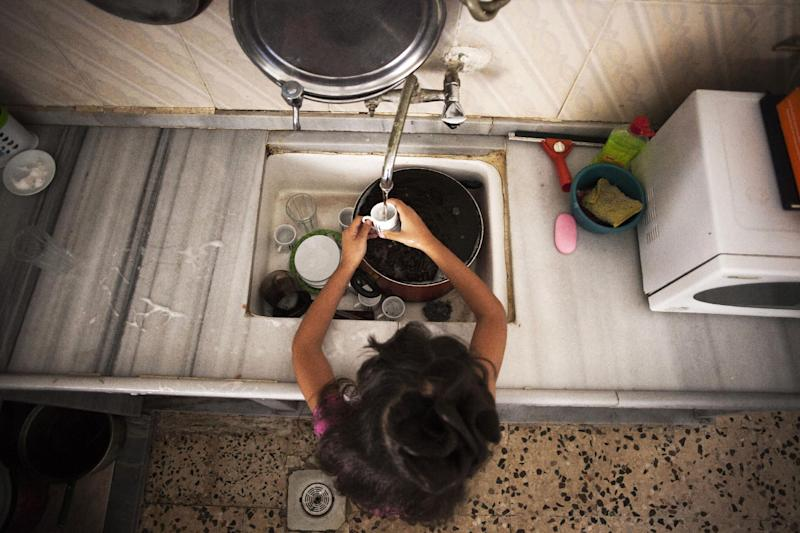 In this Monday, Oct. 21, 2013 photo, Syrian refugee Aya, 9, washes the dishes at her family's house in Zarqa, Jordan's industrial center where thousands of Syrian refugees are living, northeast of the capital Amman. Aya and her family fled from the Syrian city of Hama to Jordan in December 2011, when she was in first grade. There's no place for Aya in Jordan's public schools, already bursting at the seams with refugee children.(AP Photo/Manu Brabo)