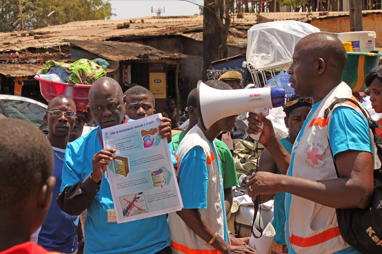 "Health workers teach people about the Ebola virus and how to prevent infection, in Conakry, Guinea, Monday, March 31, 2014. Health authorities in Guinea are facing an ""unprecedented epidemic"" of Ebola, the international aid group Doctors Without Borders warned Monday as the death toll from the disease that causes severe bleeding reached 78. The outbreak of Ebola in Guinea poses challenges never seen in previous outbreaks that involved ""more remote locations as opposed to urban areas,"" said Doctors Without Borders. (AP Photo/ Youssouf Bah)"