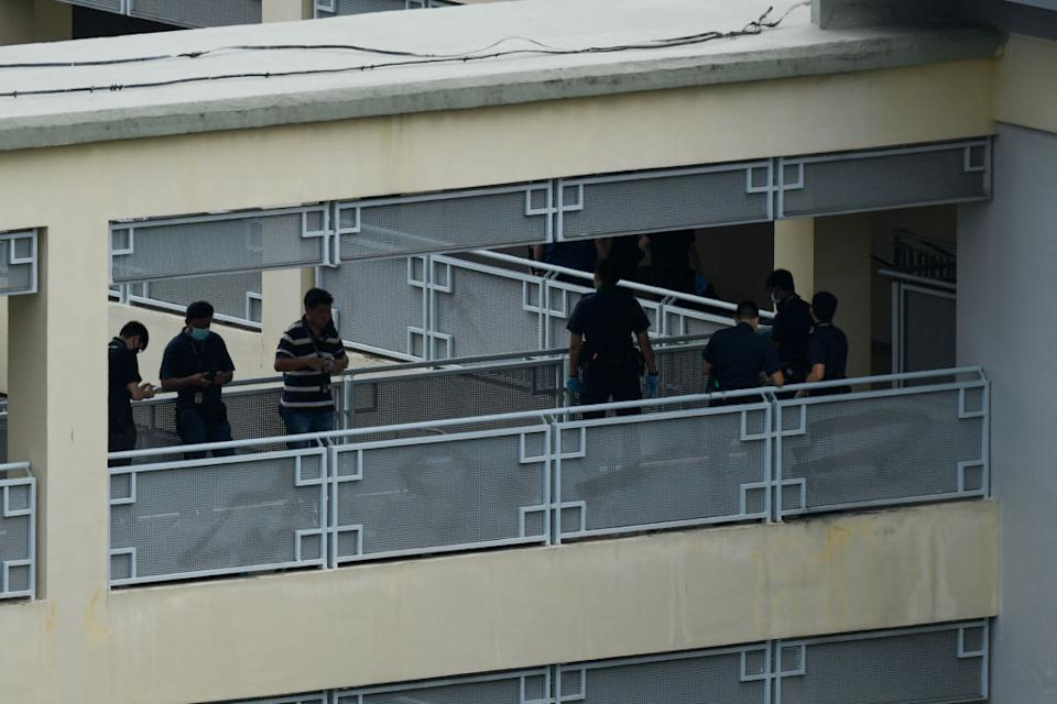 Police officers are seen along a corridor at River Valley High School in Singapore after a 13-year-old boy was found dead on the premises with multiple wounds, while a fellow student was arrested and an axe seized, police said.