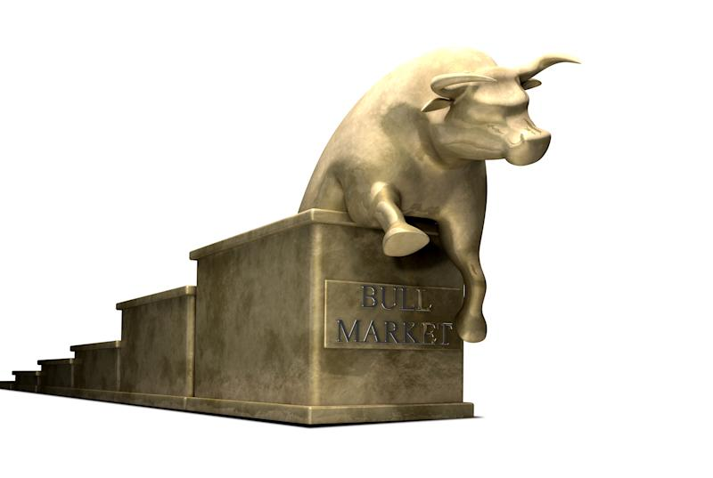 A golden bull sitting on top of a series of steps with a plaque that reads bull market on the step below the bull.