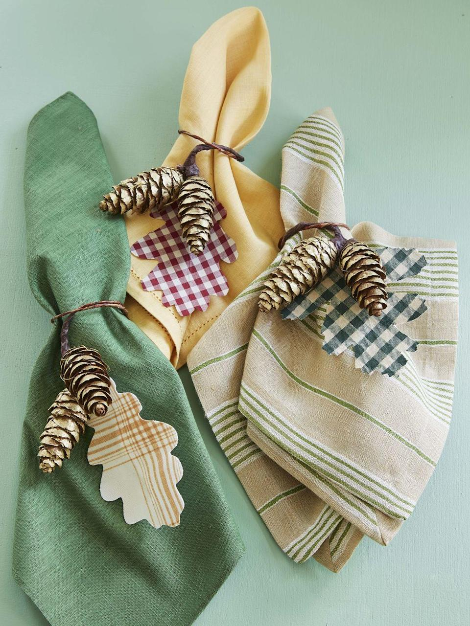 """<p>Oak-shaped leaves cut from scraps of fabric get tied up with mini pine cones that have been spray painted gold. Tie around corresponding color napkins with leather cording for an on-point table setting.</p><p><a class=""""link rapid-noclick-resp"""" href=""""https://www.amazon.com/Faux-Leather-Cord-Thread-Bracelet/dp/B07BGHV919/ref=sr_1_3?linkCode=ogi&tag=syn-yahoo-20&ascsubtag=%5Bartid%7C10050.g.2063%5Bsrc%7Cyahoo-us"""" rel=""""nofollow noopener"""" target=""""_blank"""" data-ylk=""""slk:SHOP LEATHER CORDING"""">SHOP LEATHER CORDING</a></p>"""