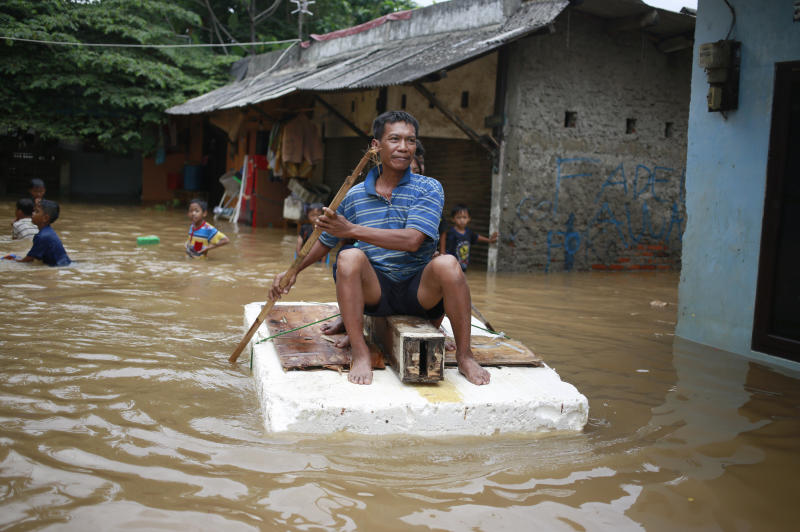 An Indonesian man sits on a raft at a flooded neighborhood in Jakarta, Indonesia, Tuesday, Feb. 21, 2017. Torrential rains in the Indonesian capital have overwhelmed drains and flooded roads and thousands of homes. Floods and deadly landslides are a fact of life for Indonesians during the wet season, with other major cities suffering repeated flooding. (AP Photo/Dita Alangkara)