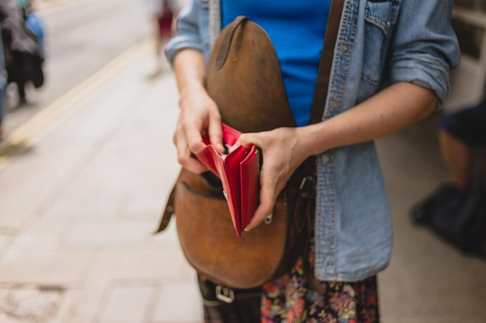 A young woman is standing in the street and is opening her purse to make a purchase