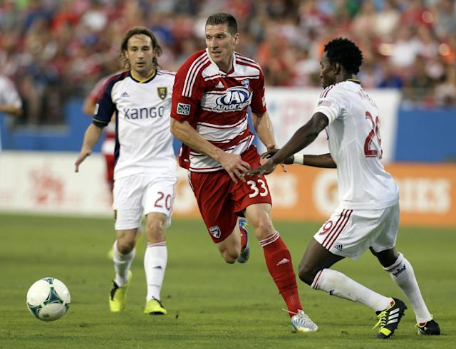 FC Dallas forward Kenny Cooper (33) chases after a loose ball past Real Salt Lake midfielder Abdoulie Mansally (29) and Ned Grabavoy (20) in the first half of an MLS soccer game on Saturday, July 13, 2013, in Frisco, Texas. (AP Photo/Tony Gutierrez)