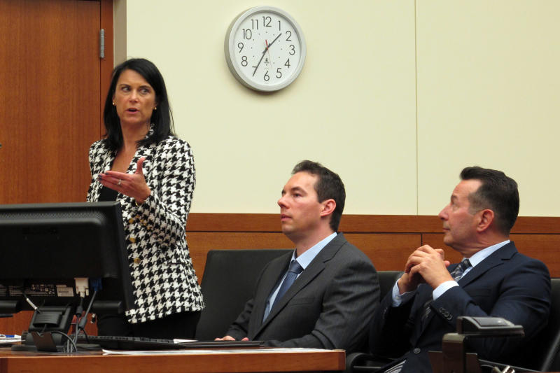 Fired doctor William Husel, center, sits between his defense lawyers, Diane Menashe and Jose Baez, during a court hearing Wednesday, Aug. 28, 2019, in Columbus, Ohio. Husel is accused of ordering excessive painkiller doses for hospital patients and has pleaded not guilty to 25 counts of murder.(AP Photo/Kantele Franko)