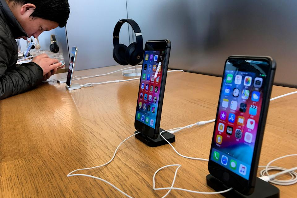 A man tries out a latest iPhone next to iPhone 8 and 8 Plus on display for sale at an Apple Store in Beijing, Tuesday, Dec. 11, 2018. (AP Photo/Andy Wong)