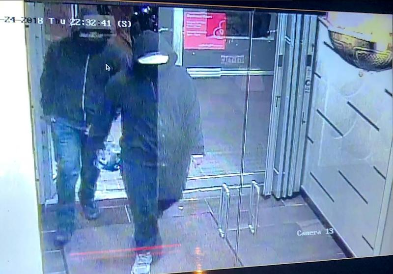Police just outside Toronto released a surveillance camera image of two hooded men carrying a device and entering an Indian restaurant where a blast occurred, wounding 15 people