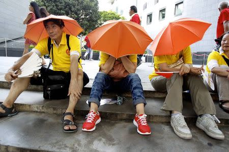 Pro-Beijing protesters rest after taking part in a march to demonstrate against a pro-democracy Occupy Central campaign in Hong Kong