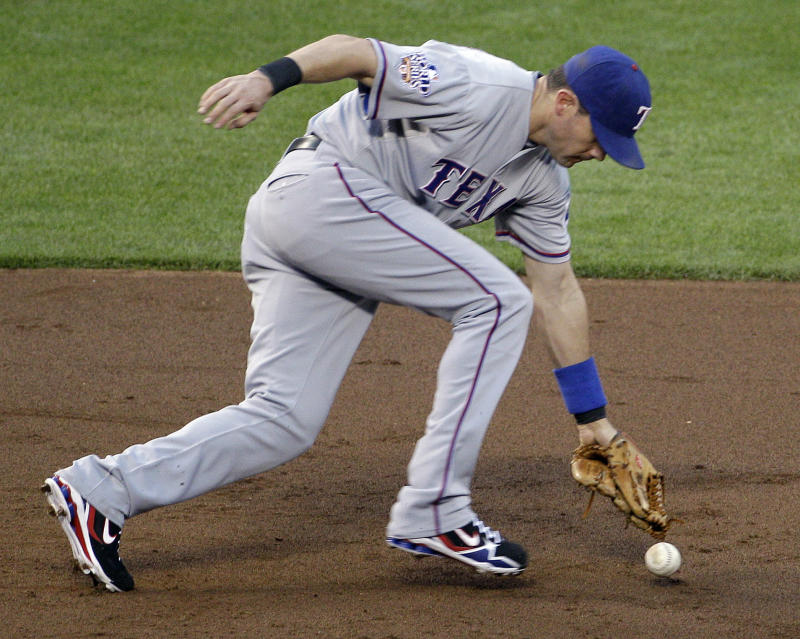 Texas Rangers' Michael Young can't catch a single by San Francisco Giants' Edgar Renteria during the third inning of Game 1 of baseball's World Series Wednesday, Oct. 27, 2010, in San Francisco. (AP Photo/Eric Risberg)