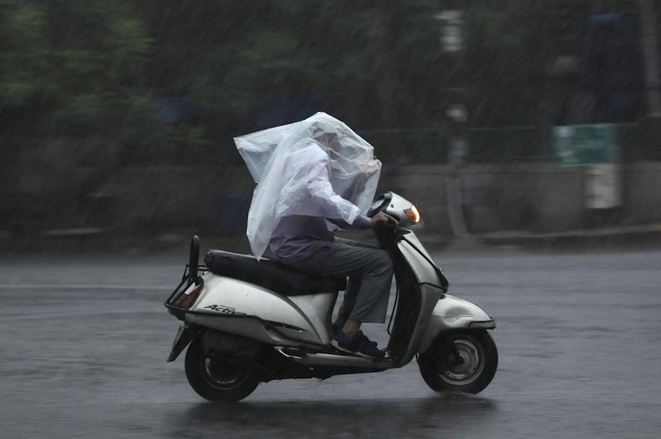 A motorist driving with a plastic sheet for cover during rain at sector 19, on July 19, 2020 in Noida, India. Moderate-to-heavy rain lashed several states in northern, eastern and coastal India on Sunday, but the monsoon activity continued to remain subdued in Delhi, which has recorded a 40 per cent rainfall deficiency despite an early onset of the seasonal weather system. (Photo By Sunil Ghosh/Hindustan Times via Getty Images)