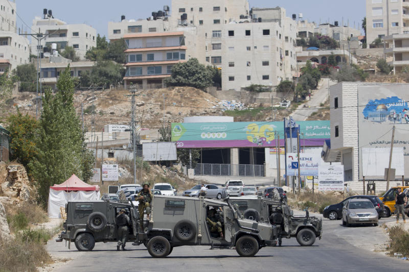 Israeli forces close the roads near the area of an attack, west of the West Bank city of Ramallah, Friday, Aug. 23. 2019. An explosion Friday near a West Bank settlement that Israel said was a Palestinian attack killed a 17-year-old Israeli girl and wounded her brother and father, Israeli authorities said. (AP Photo/Nasser Nasser)
