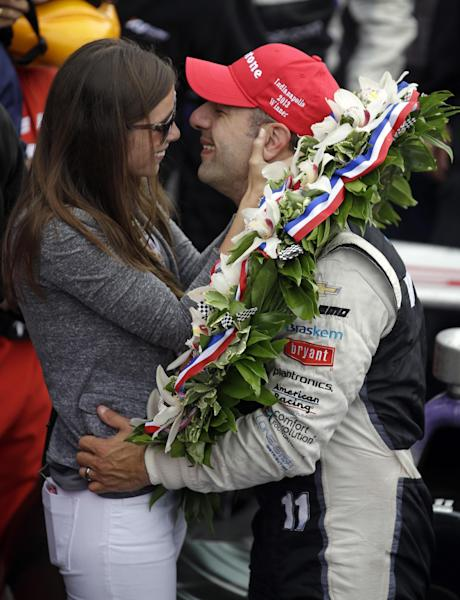 Tony Kanaan, of Brazil, kisses his wife Lauren Bohlander Kanaan after winning the Indianapolis 500 auto race at the Indianapolis Motor Speedway in Indianapolis, Sunday, May 26, 2013. (AP Photo/Michael Conroy)