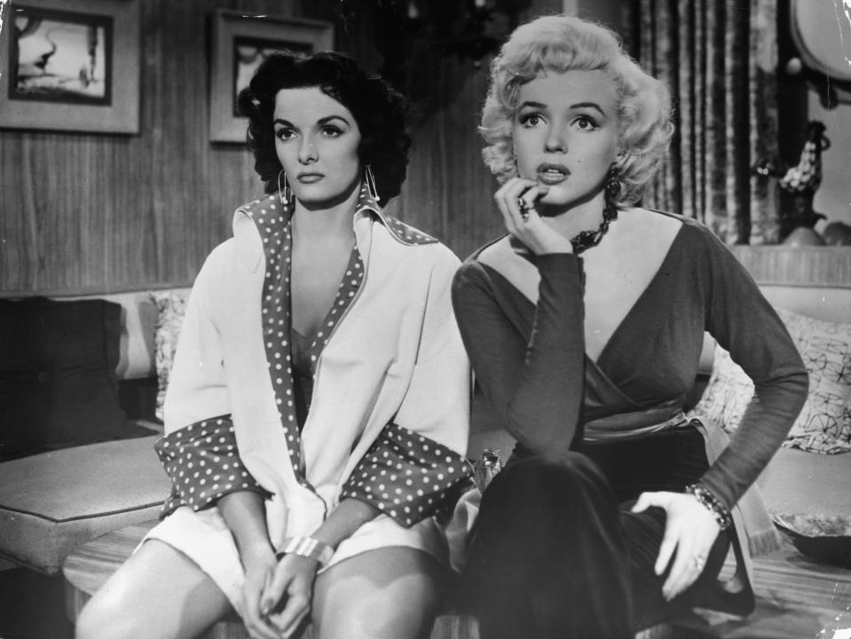 Jane Russell and Marilyn Monroe sitting on table together in a scene from the film 'Gentlemen Prefer Blondes', 1953. (Photo by 20th Century-Fox/Getty Images)