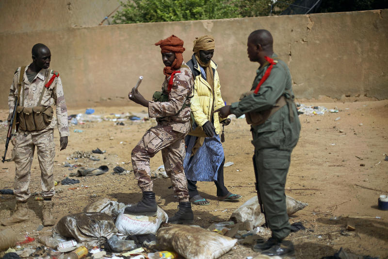 Malian soldiers inspect a stick of Nitram 5 explosive they found  Wednesday Feb. 6, 2013, after residents notified authorities of suspicious bags left by Mujao radicals when they fled Gao, northern Mali. Troops from France and Chad moved into Kidal in an effort to secure the strategic north Malian city, a French official said Tuesday, as the international force put further pressure on the Islamic extremists to push them out of their last major bastion of control in the north. (AP Photo/Jerome Delay)