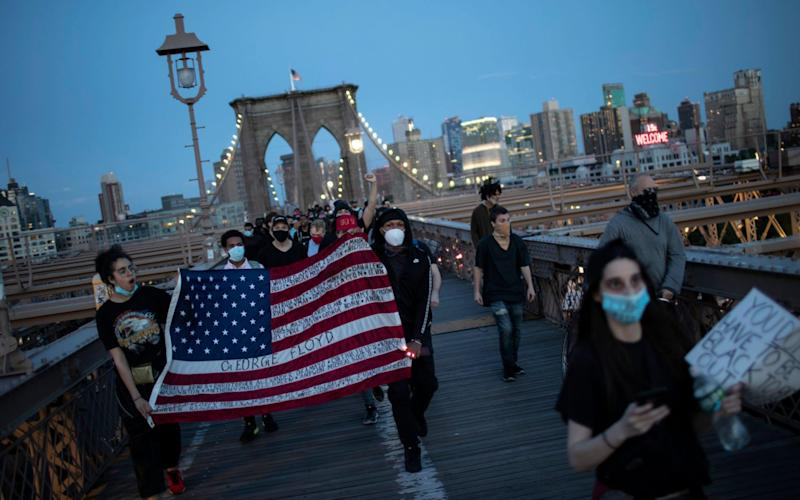 Protesters march across the Brooklyn Bridge as part of a solidarity rally calling for justice over the death of George Floyd - AP
