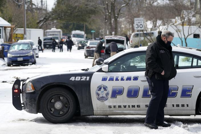 A Dallas police officer patrols an intersection on the 5300 block of Bonita Avenue in Dallas, Thursday, Feb. 18, 2021. Earlier in the day, two Dallas officers were shot responding to an emergency at a home on the block. (AP Photo/Tony Gutierrez)