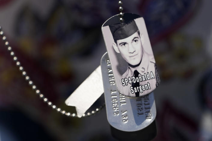 A relative of SP4 Donald Sargent wears his dog tags at the unveiling of a monument to honor the military passengers of Flying Tiger Line Flight 739, Saturday, May 15, 2021, in Columbia Falls, Maine. Sargent, was among those killed on the secret mission to Vietnam in 1962. (AP Photo/Robert F. Bukaty)