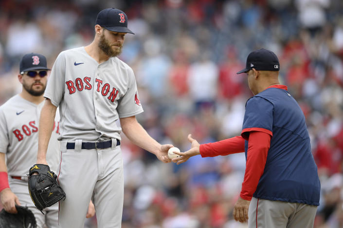 Boston Red Sox starting pitcher Chris Sale, left, is pulled from the game by manager Alex Cora, right, during the third inning of a baseball game against the Washington Nationals, Sunday, Oct. 3, 2021, in Washington. (AP Photo/Nick Wass)
