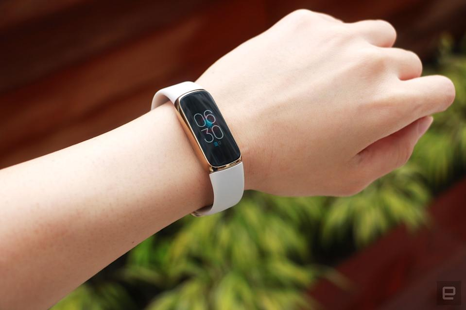 <p>Slight off angle view of the Fitbit Luxe with a light pink silicone band on a wrist against a dark brown background with some greenery. The screen shows the time is 6:30pm.</p>