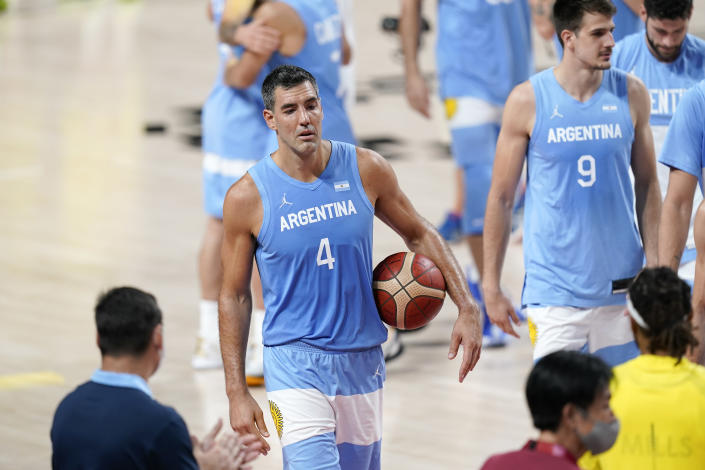 Argentina's Luis Scola (4) walks off the court with the game ball after a men's basketball quarterfinal round game against Australia at the 2020 Summer Olympics, Tuesday, Aug. 3, 2021, in Saitama, Japan. (AP Photo/Charlie Neibergall)