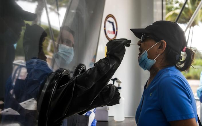 (FILES) In this file photo taken on July 24, 2020 nurse practitioner Raciel Gomez (L) swabs the nose of Jeewan Prabha Mehta through a glass pane at the Aardvark Mobile Health's Mobile Covid-19 Testing Truck in Miami Beach. - Florida has emerged as a major new epicenter of the US coronavirus battle, but two key weapons in the state's fight are misfiring badly: testing and contact tracing. (Photo by CHANDAN KHANNA / AFP) (Photo by CHANDAN KHANNA/AFP via .) - AFP