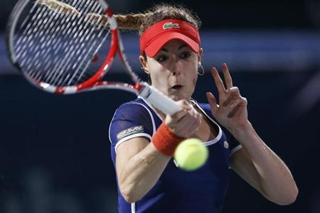 Alize Cornet of France returns the ball to Serena Williams of the U.S. during their women's singles semi-final match at the WTA Dubai Tennis Championships
