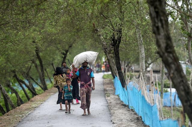 """Residents walk along a street heading to a shelter ahead of the expected landfall of cyclone Amphan, in Dacope of Khulna district on May 20, 2020. - Several million people were taking shelter and praying for the best on Wednesday as the Bay of Bengal's fiercest cyclone in decades roared towards Bangladesh and eastern India, with forecasts of a potentially devastating and deadly storm surge. Authorities have scrambled to evacuate low lying areas in the path of Amphan, which is only the second """"super cyclone"""" to form in the northeastern Indian Ocean since records began. (Photo by Munir uz Zaman / AFP) (Photo by MUNIR UZ ZAMAN/AFP via Getty Images)"""