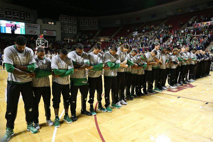 Players and coaches for the Boston Celtics crossed arms and held hands during the National Anthem. (Chris Marion/Getty Images)