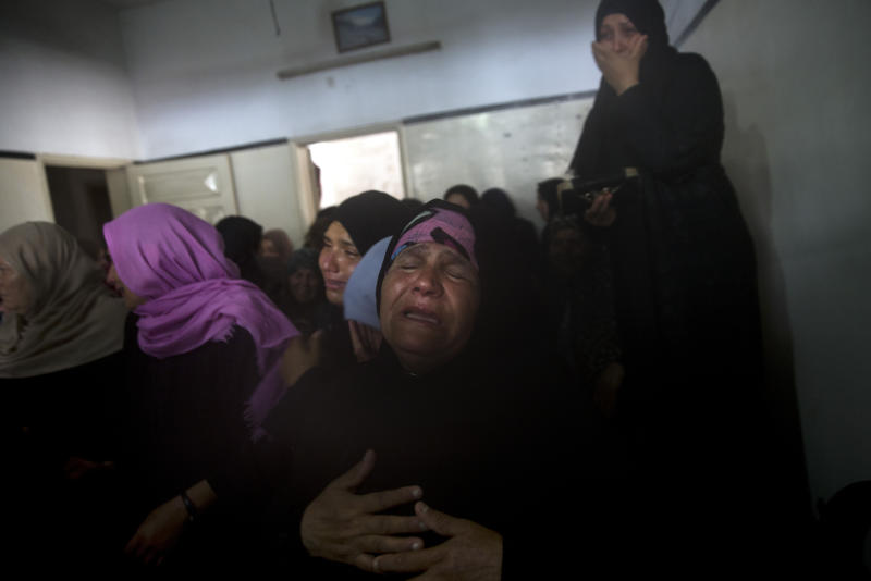 "Relatives of Hamas security forces member, Mahmoud al-Adham, 28, mourn over his body during his funeral inside his home, in the town of Jabaliya, northern Gaza Strip, Thursday, July 11, 2019. Hamas' armed wing said Thursday that Israeli the army ""deliberately"" fired at al-Adham, in the northern town of Beit Hanoun. The Israeli military said it noticed two ""armed suspects"" near the Gaza-Israel perimeter fence and responded with warning shots. (AP Photo/Khalil Hamra)"