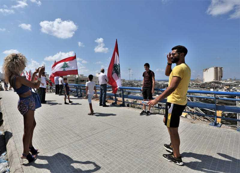 People stand next to Lebanese flags on a bridge overlooking the damaged Beirut port and grain silos, in Beirut, Lebanon.