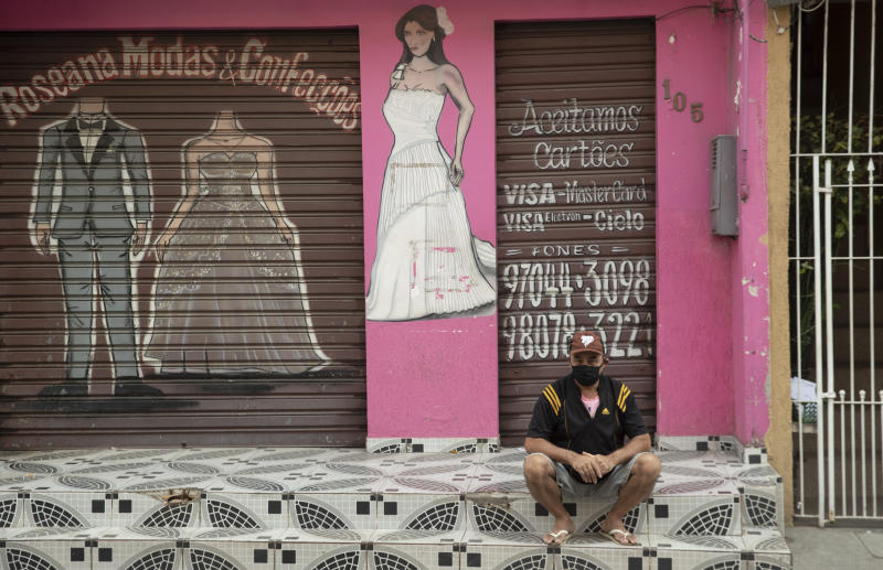 A man sits outside a shuttered store, closed due to the lockdown aimed at curbing the spread of the new coronavirus in the Paraisopolis slum of Sao Paulo, Brazil, Wednesday, May 6, 2020. With over 100,000 residents, Paraisopolis is one of the areas most affected by COVID-19 in Sao Paulo. (AP Photo/Andre Penner)