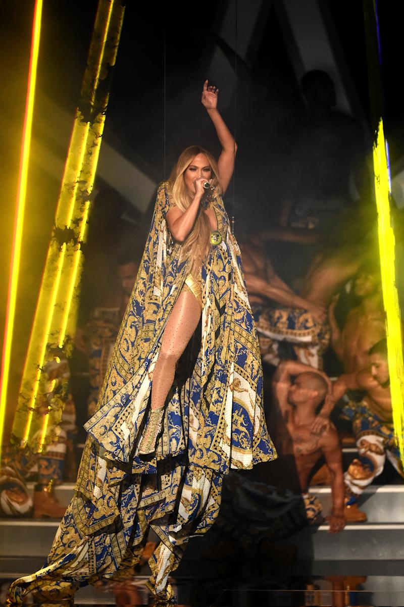 The artist descended from the ceiling as she started the performance in a long cape before kicking it off to reveal a gold bodysuit.  (Michael Loccisano via Getty Images)