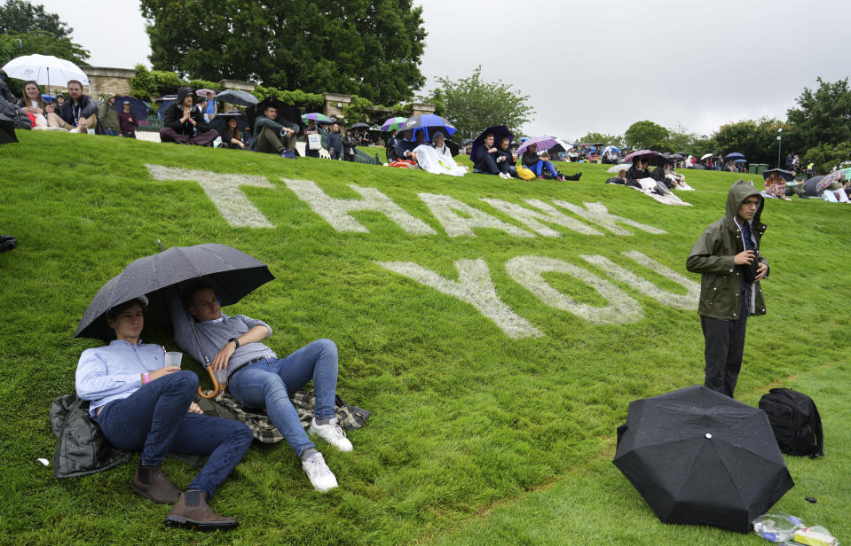Spectators shelter under umbrellas during a rain delay on day one of the Wimbledon Tennis Championships in London, Monday June 28, 2021. (AP Photo/Alberto Pezzali)