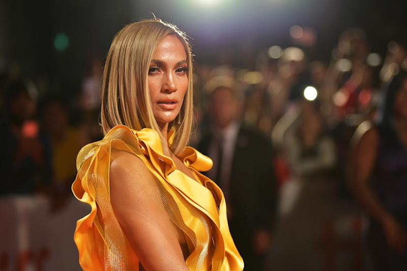 Jennifer Lopez shows off her tanned skin in this lovely photo and she looks amazing in this yellow arm-less dress