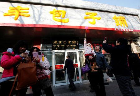 FILE PHOTO: Visitors take pictures for remembrance at the Qing-Feng steamed buns restaurant where Chinese President Xi visited and dined at, in Beijing