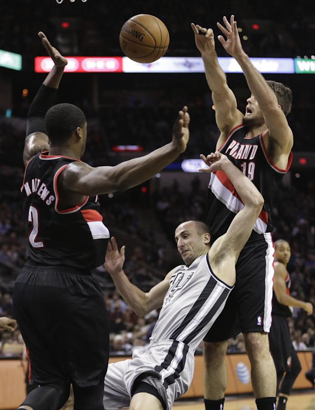 San Antonio Spurs' Manu Ginobili (20), of Argentina, is fouled as he drives between Portland Trail Blazers' Wesley Matthews (2) and Joel Freeland, right, during the first half on an NBA basketball game, Friday, Jan. 17, 2014, in San Antonio. (AP Photo/Eric Gay)