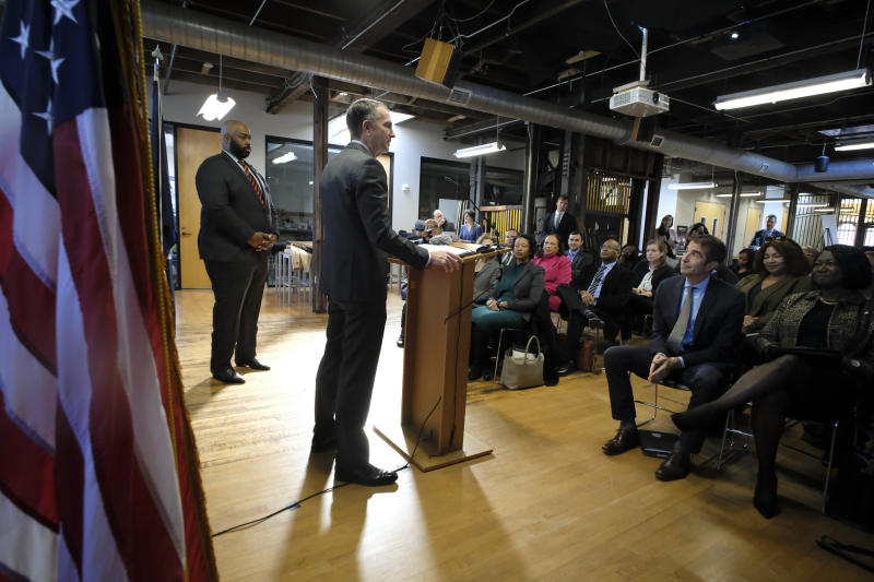 As Del. Lamont Bagby, D-Henrico, left, looks on, Gov. Ralph Northam, at podium, addresses a gathering after receiving the report from The Commission to Examine Racial Inequity in Richmond, Va., Thursday, Dec. 5, 2019. (Bob Brown/Richmond Times-Dispatch via AP)