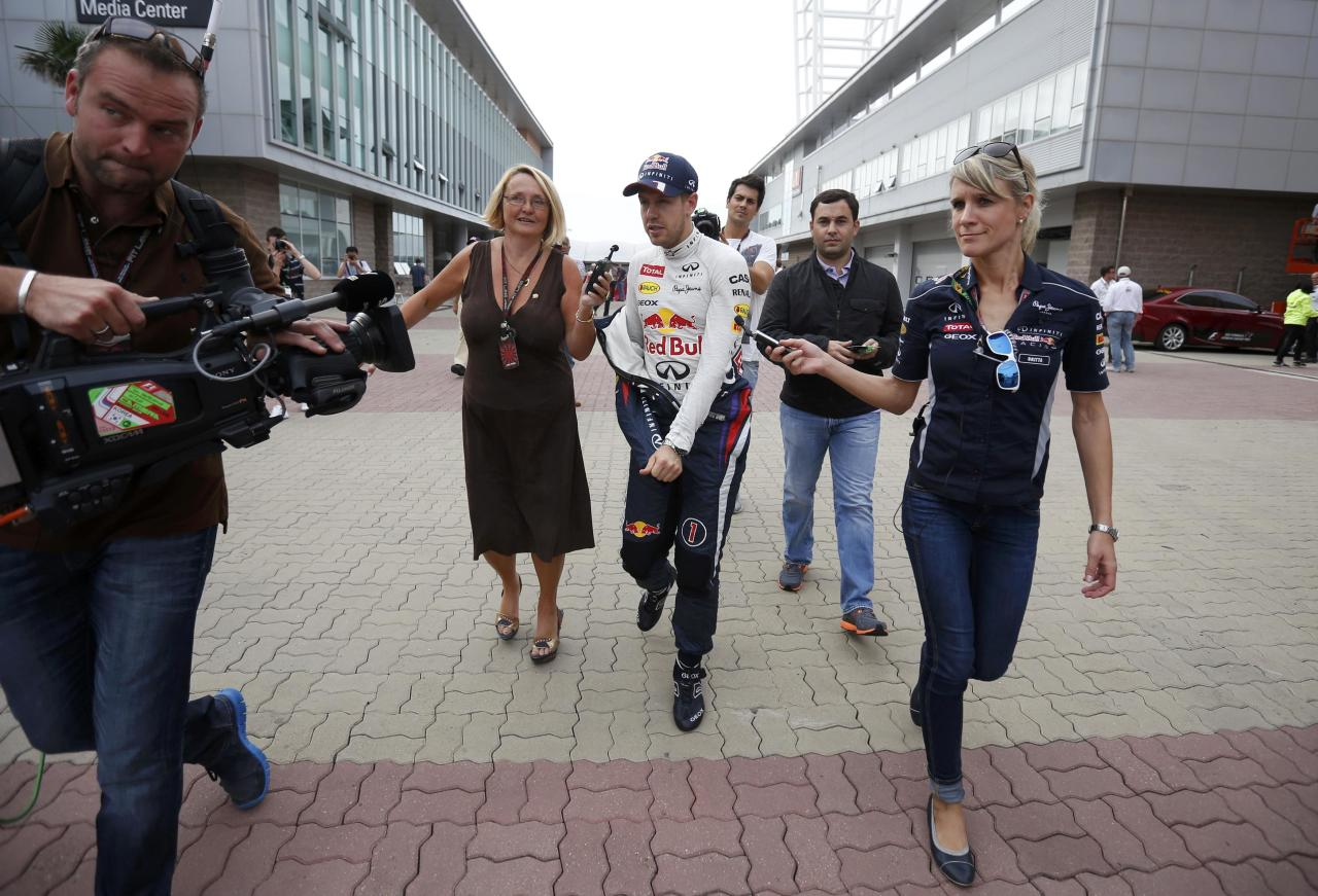 Red Bull Formula One driver Sebastian Vettel of Germany (center R) is being interviewed on the run after the qualifying session for the Korean F1 Grand Prix at the Korea International Circuit in Yeongam, October 5, 2013. REUTERS/Kim Hong-Ji (SOUTH KOREA - Tags: SPORT MOTORSPORT F1)