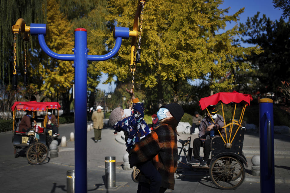 A woman holds a child, both wearing face masks to help curb the spread of the coronavirus play on an exercise equipment as masked trishaw drivers wait for customers near the Houhai Lake in Beijing, Sunday, Nov. 8, 2020. (AP Photo/Andy Wong)