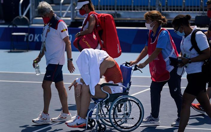 Paula Badosa had to leave the court in a wheelchair after suffering in the heat - AP