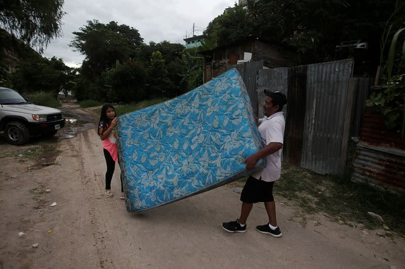 Residents carry a mattress as they evacuate their house in anticipation of heavy rains as Hurricane Iota approaches, in Tegucigalpa
