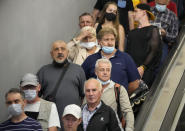 FILE - In this June 29, 2021, file photo, people ride the escalator in the subway amid the ongoing COVID-19 pandemic in St. Petersburg, Russia. Countries across Europe are scrambling to accelerate coronavirus vaccinations to outpace the spread of the delta variant in a high-stakes race to prevent hospital wards from filling up again with patients fighting for their lives. Daily new case numbers are already climbing sharply in countries like the United Kingdom, Portugal and Russia. (AP Photo/Dmitri Lovetsky, File)