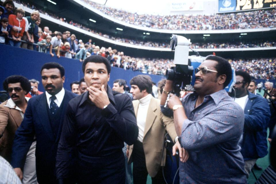 World Heavyweight Boxing Champion Muhammad Ali (c) is filmed as he walks out at Giants Stadium with his brother Rahaman (second l) to greet Pele before the Brazilian star's final match of his career  (Photo by Peter Robinson/EMPICS via Getty Images)