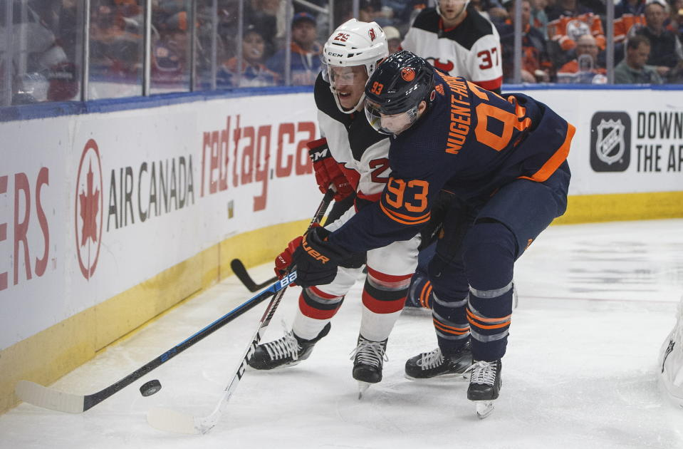 New Jersey Devils' Mirco Mueller (25) and Edmonton Oilers' Ryan Nugent-Hopkins (93) compete for the puck during the second period of an NHL hockey game Friday, Nov. 8, 2019, in Edmonton, Alberta. (Jason Franson/The Canadian Press via AP)