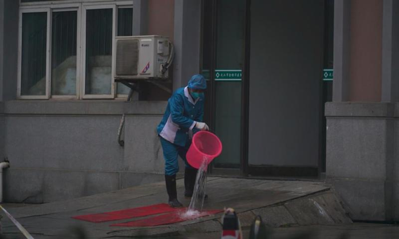 Hospital staff wash the emergency entrance of Wuhan Medical Treatment Center, where some infected with the new virus are being treated